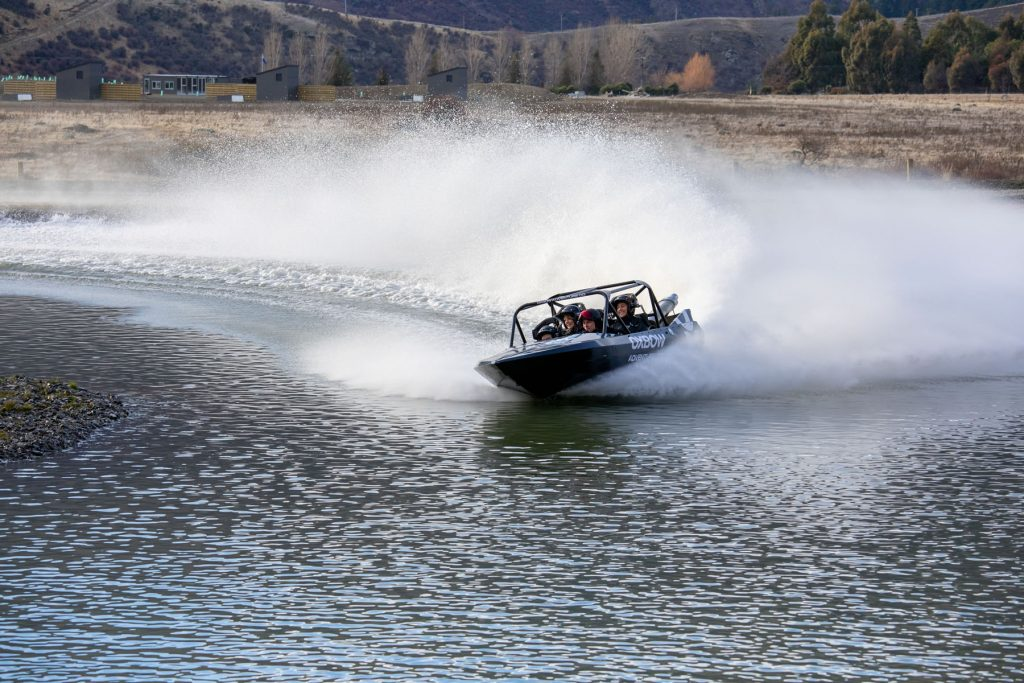 Jet sprint boat in action with thrilled adventurers