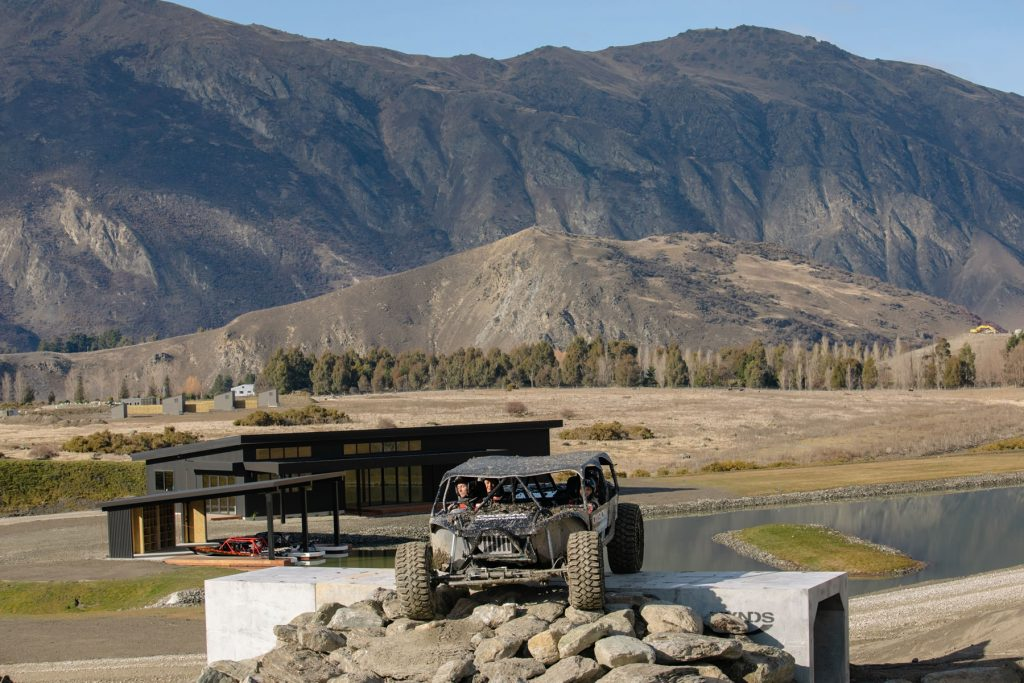 Off road vehicle with headquarters and stunnning scenery and terrain in the background