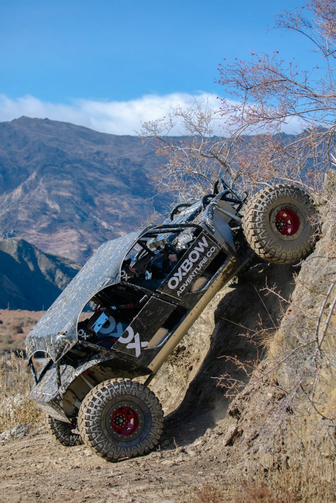 Off-road vehicle in full action going up a steep piece of terrain